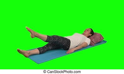 Woman in white t-shirt doing rehabilitation exercise while lying at blue mat raising leg and knee flexed to 90 against green screen at studio.