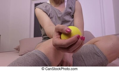 Woman doing rehabilitation exercises with stress ball