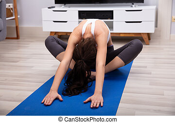 Woman Doing Relaxation Exercise On Exercise Mat At Home