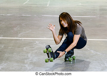 woman doing shoot the duck move on quad roller skates in an arena