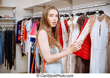 Woman doing shopping and choosing dress in clothing store