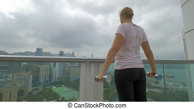 Woman doing shoulder exercises on the balcony. Hong Kong, China