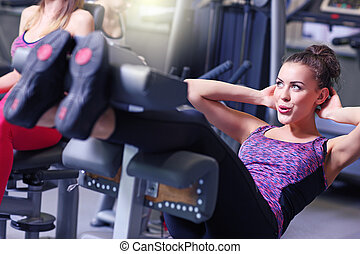 Woman doing sit ups in gym