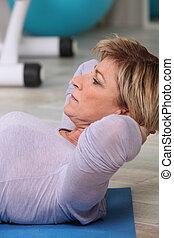 Woman doing sit-ups on gym mat