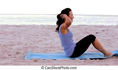 Woman doing sit ups on the beach
