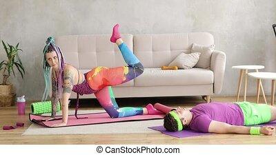 Woman doing sport exercise for legs on mat, man lying resting on mat near her.