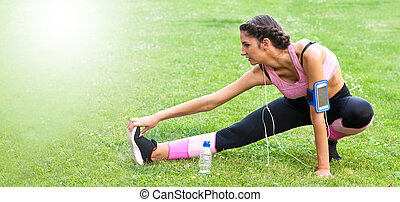woman doing sports outdoors with mobile phone