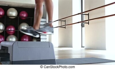 Woman doing step jumps at the gym. Slow motion