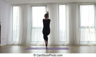 Woman doing stretching exercise in a yoga studio