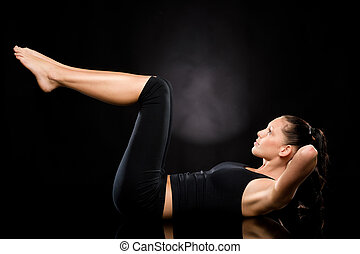Woman doing stretching exercise with raised legs