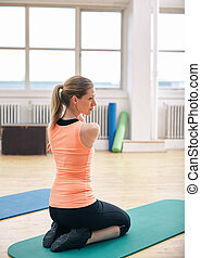 Woman doing stretching exercises at gym