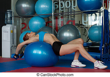 Woman doing stretching exercises on gymnastic ball