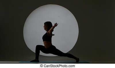 Woman doing stretching. Sports exercise. Back light. Silhouette