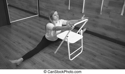 Woman doing stretching while sitting in the splits. Black...