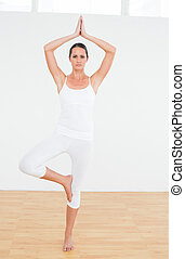 Woman doing the tree pose at a fitness studio