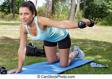 woman doing various exercises with dumbbell and mat