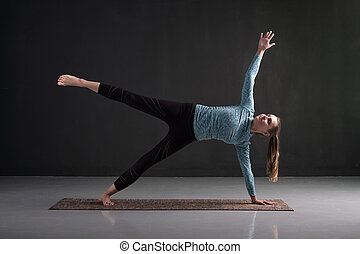 Woman doing Vasisthasana or Side Plank yoga pose