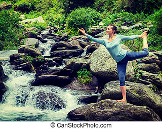 Woman doing yoga asana Natarajasana outdoors at waterfall -...