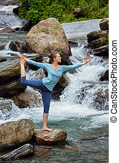 Woman doing yoga asana Natarajasana outdoors at waterfall -...