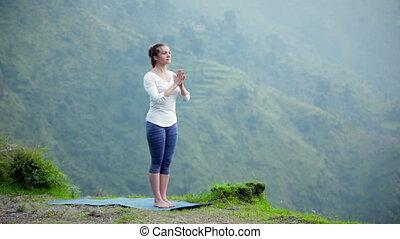 Woman doing yoga asana tree pose outdoors