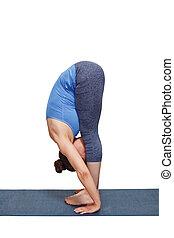 Woman doing yoga asana Uttanasana - standing forward bend