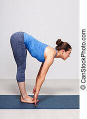 Woman doing yoga asana Uttanasana - standing forward bend...