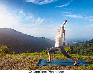 Woman doing yoga asana Virabhadrasana 1 - Warrior pose outdoors
