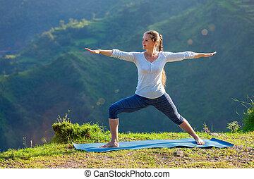 Woman doing yoga asana Virabhadrasana 2 - Warrior pose outdoors