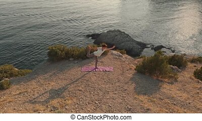 Woman doing yoga at sunset - Young woman do yoga on scenic...