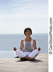 Woman doing yoga by the waterfront