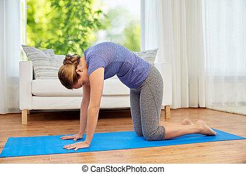 caucasian woman making simple yoga asana cow or cat