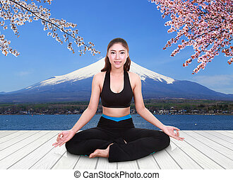 woman doing yoga exercise on wood floor with Mt Fuji and Cherry Blossom