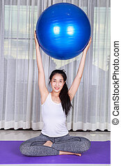 woman doing yoga exercise with fitness ball