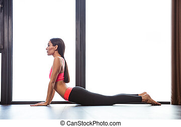 Woman doing yoga exercises in fitness gym