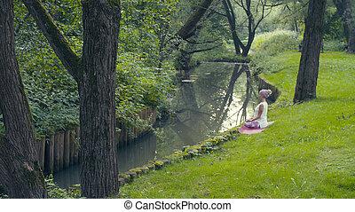 Woman doing yoga exercises near the river