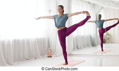 woman doing yoga hand-to-big-toe pose at studio - fitness,...