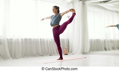 woman doing yoga hand-to-big-toe pose at studio - fitness,...