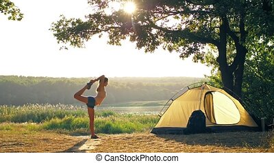 Woman doing yoga in a front of tent