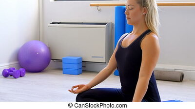Woman doing yoga in fitness gym 4k