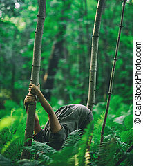 Woman doing yoga in forest bending