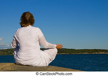 woman doing yoga in front of the ocean