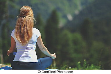 woman doing yoga meditating in the lotus position with his back in the summer
