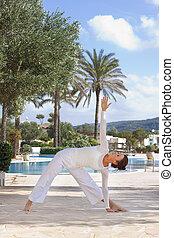 Woman doing yoga next to pool