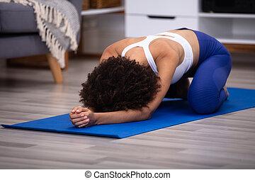 Woman Doing Yoga On Fitness Mat