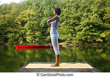 yoga - Woman doing yoga on lake in park in autumn