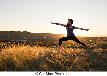 Woman doing yoga warrior II pose during sunset