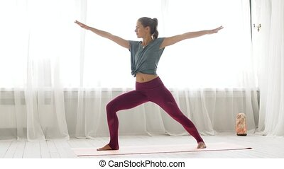 woman doing yoga warrior pose at studio - fitness, sport and...