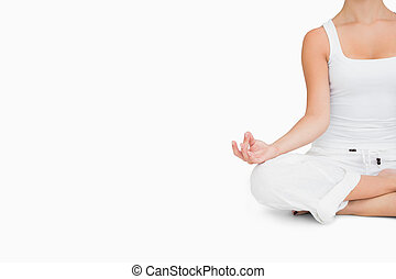 Woman doing yoga while cross-legged - Woman doing yoga pose...