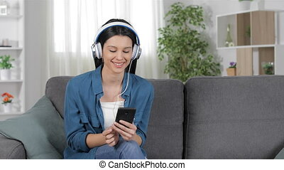 Woman downloading and listening to music at home - Happy ...