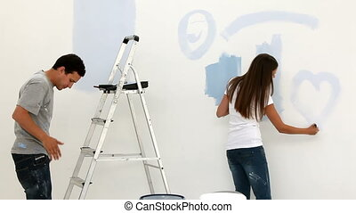 Woman drawing a heart on the wall while her husband painting
